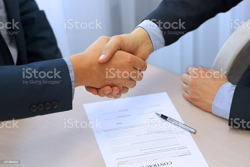 Close-up image of a firm handshake between two colleagues stock photo