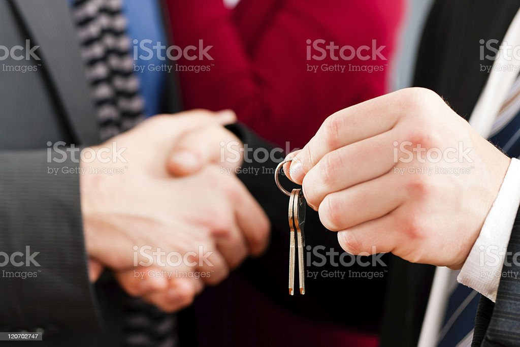 Close-up image of a man's hands passing off a set of keys stock photo