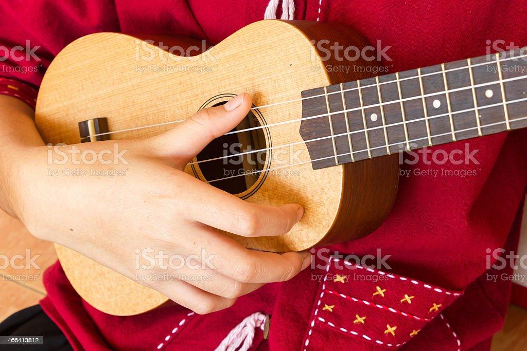 A closeup image of a teenager playing the ukulele stock photo