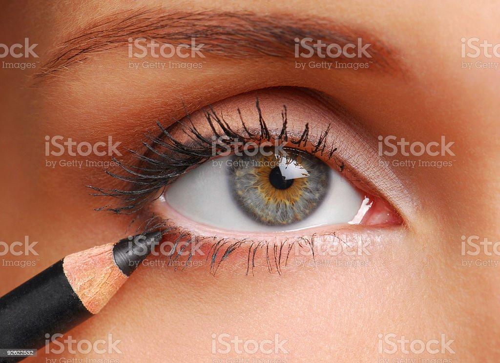 A closeup image of a woman applying black eyeliner stock photo