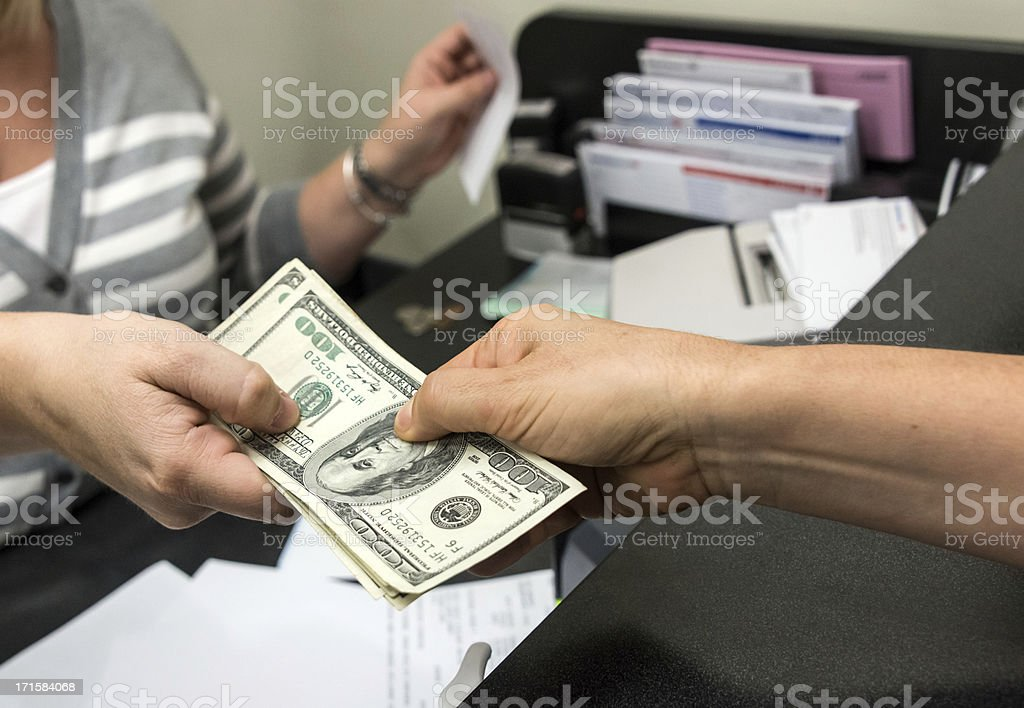 close-up image of a woman getting a cash from a bank teller stock photo