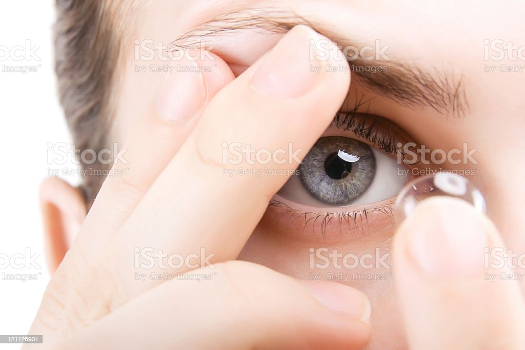 Closeup image of a woman putting a contact in her blue eye royalty-free stock photo