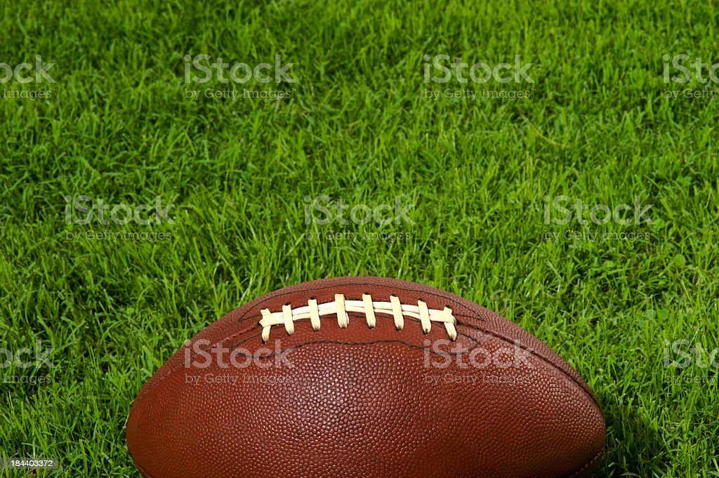 Close-up image of an American football on grassy turf royalty-free stock photo