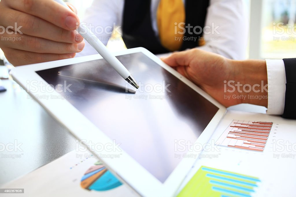 Close-up image of an office worker using touchpad to analyze stock photo
