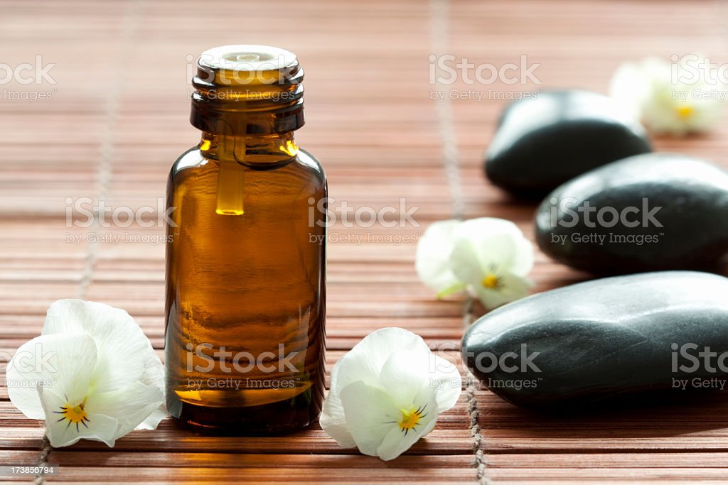 Close-up image of essential oils bottle, flowers, and stones royalty-free stock photo