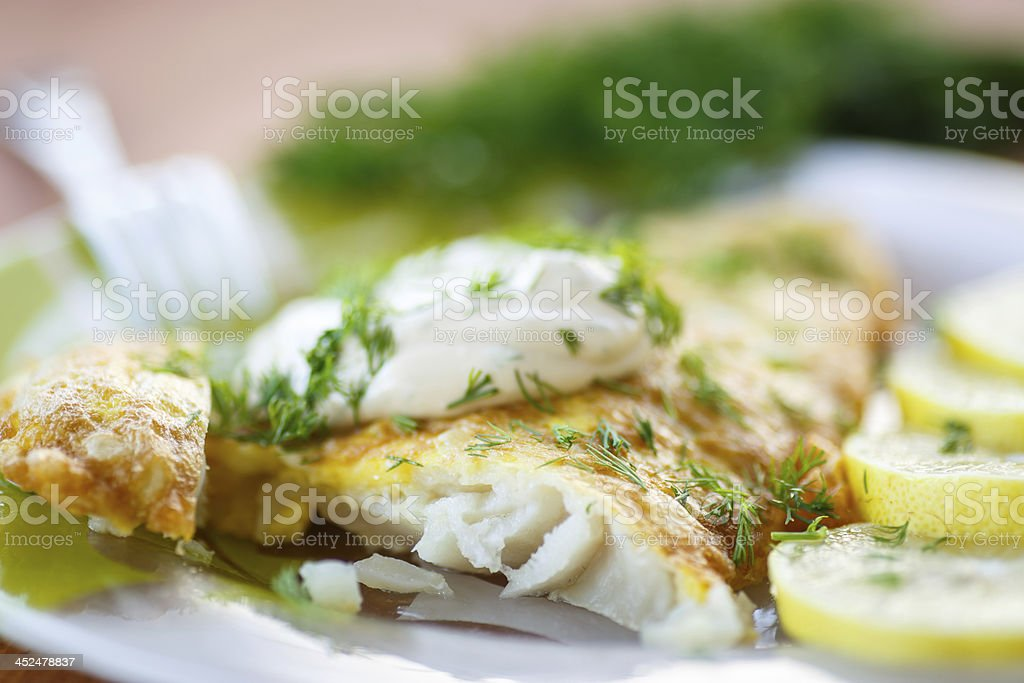 A close-up image of fried fish and lemon slices stock photo