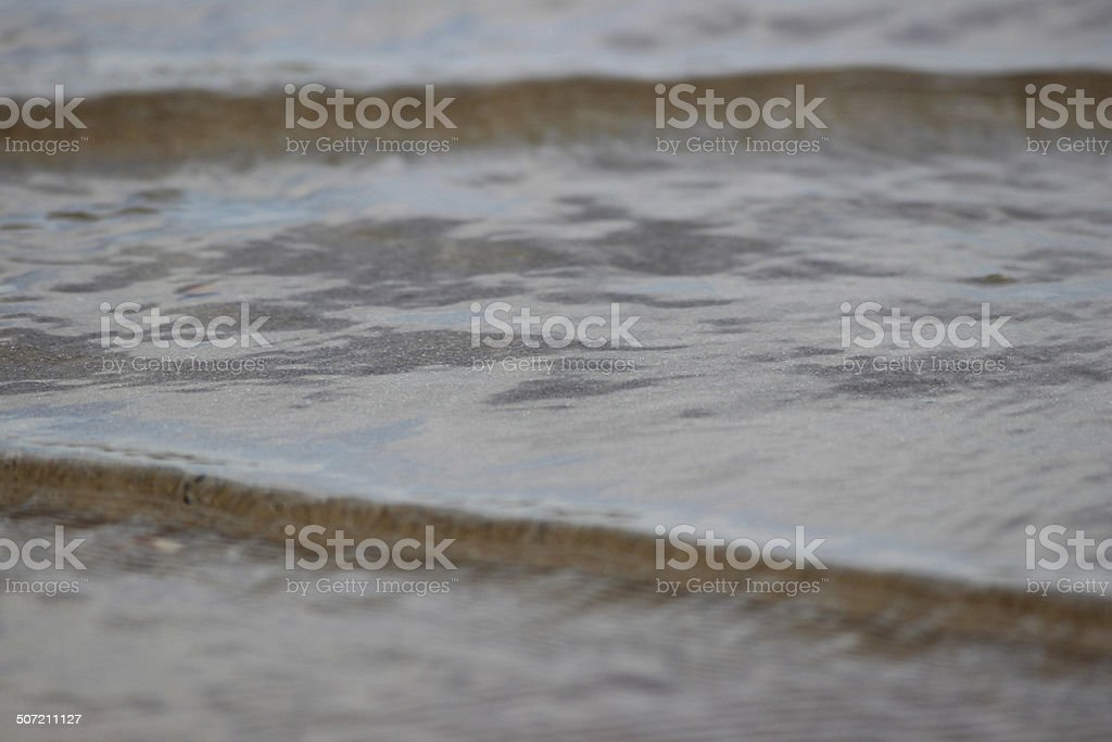 Close-up image of gentle sea waves lapping the beach shore stock photo