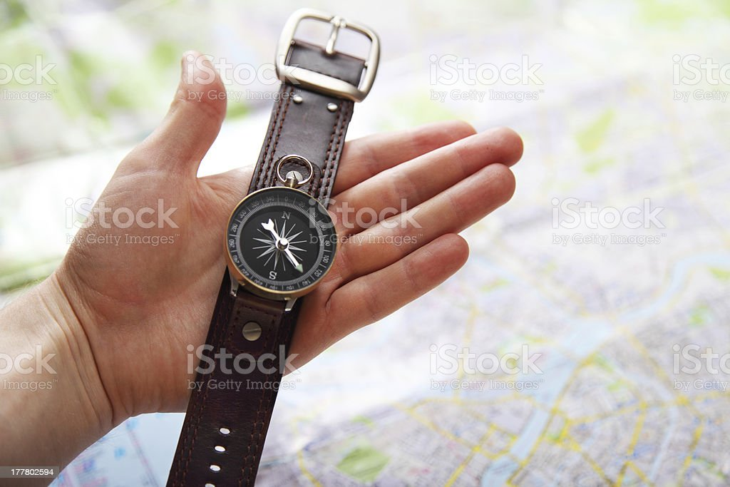 Closeup image of hand with magnetic compass over a map royalty-free stock photo
