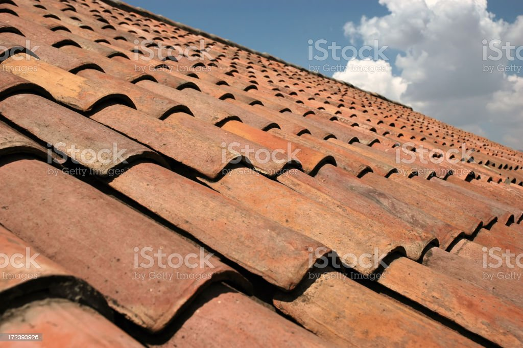 Closeup image of red roof tiles under a blue sky royalty-free stock photo