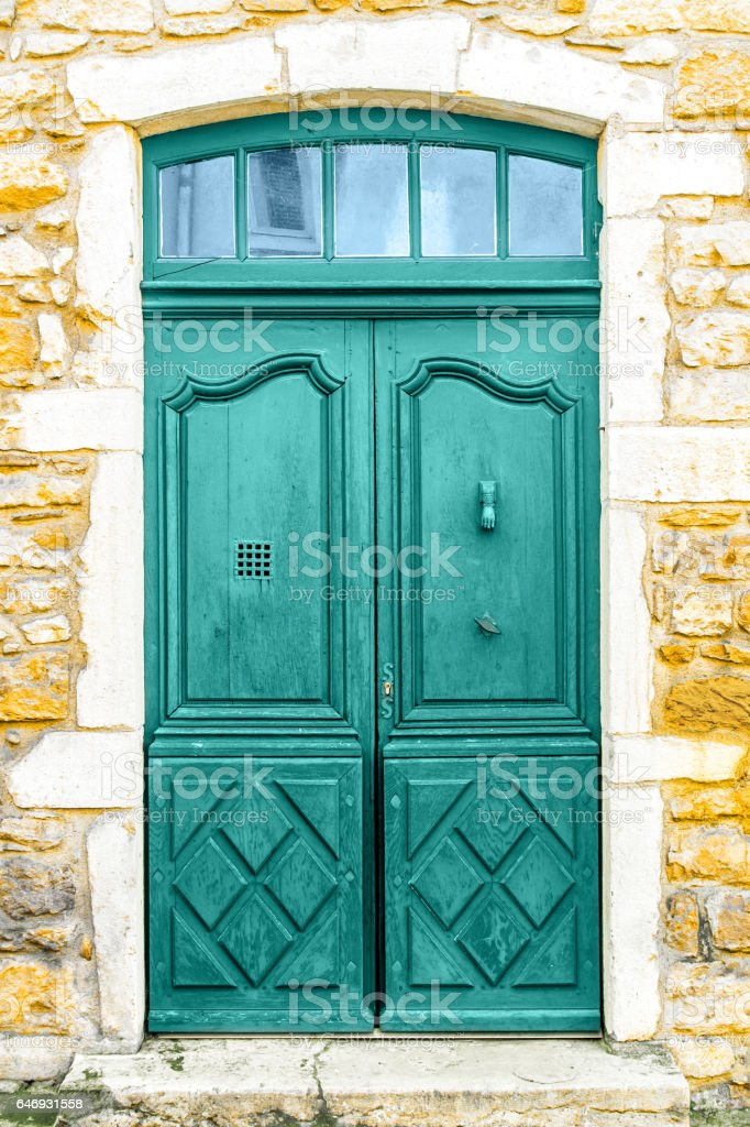 Close-up in full frame of old painted cyan green wooden door on old stone wall facade front view with small windows on top stock photo