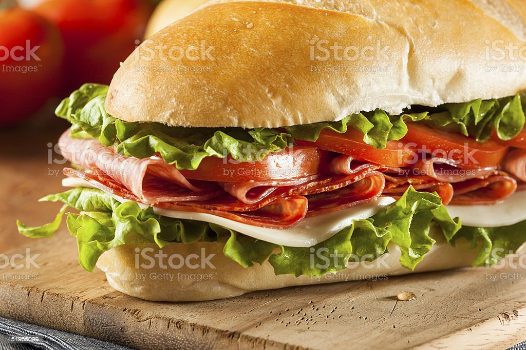 Close-up Italian sub hoagie sandwich cutting board stuffed stock photo