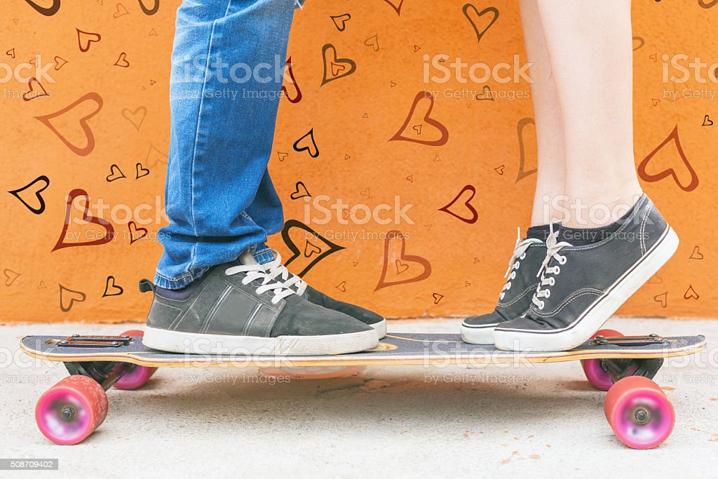 Closeup kissing couple at skateboard and red wall background stock photo