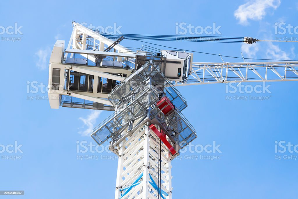 Closeup low angle view of tower crane cabin, copy space stock photo