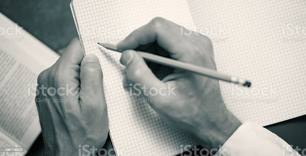 Close-up: male hands writing with a pencil on a notebook stock photo