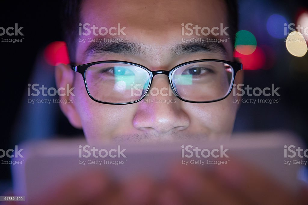 close-up man using mobile phone at night stock photo