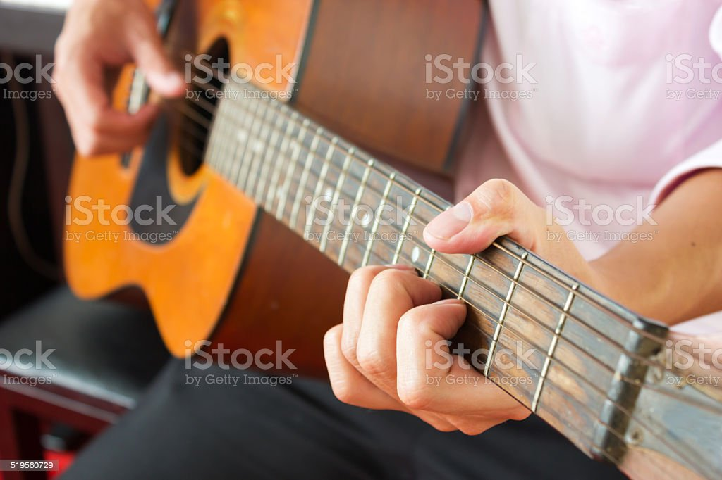 Closeup man's hands playing classic guitar. stock photo