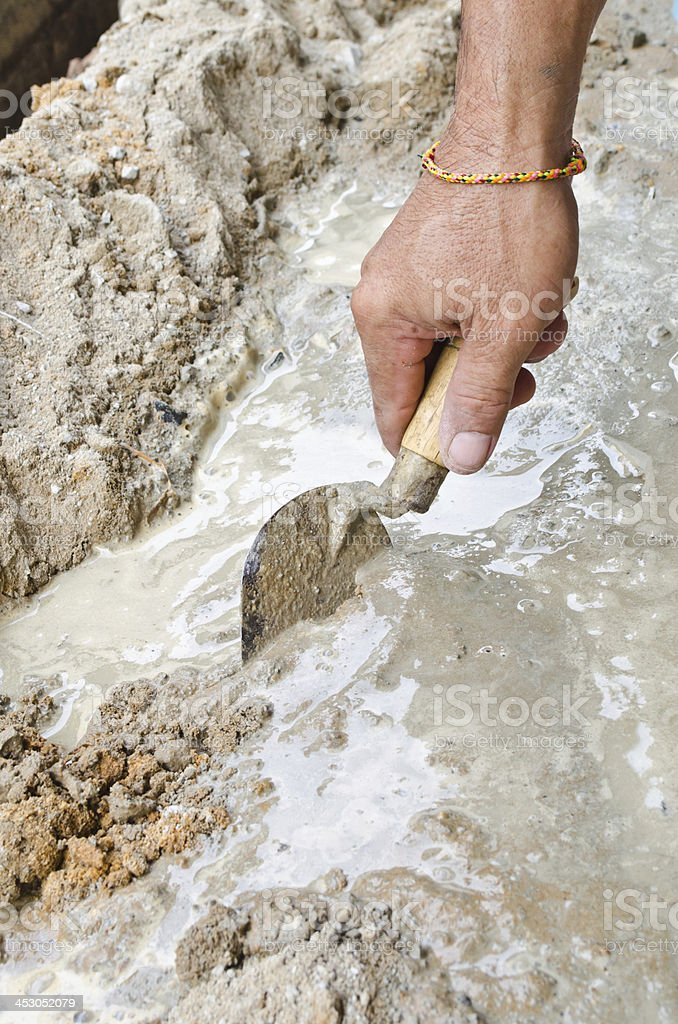 Closeup mason hand spreading fresh concrete mix with trowel royalty-free stock photo