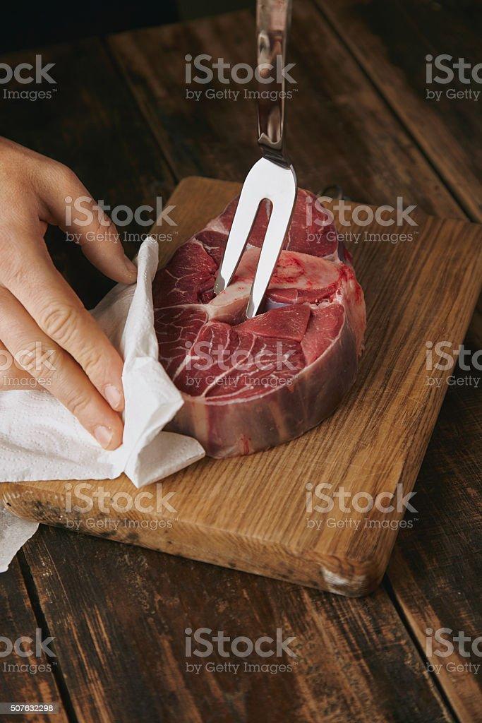 closeup meat fork in raw steak stock photo