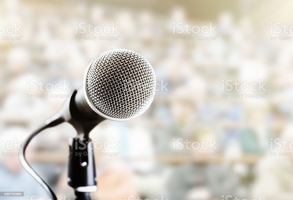 Close-up mic with defocused audience behind stock photo