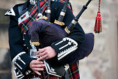 Close-up mid section of a man playing the Scottish bagpipes