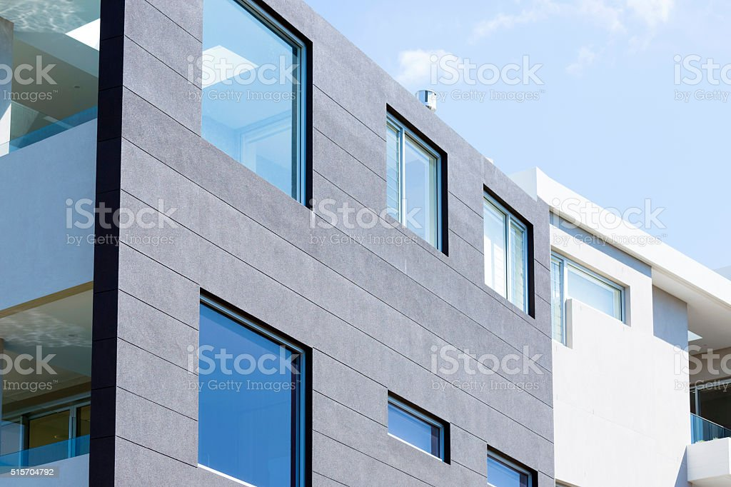 Closeup modern apartment building against blue sky, copy space stock photo