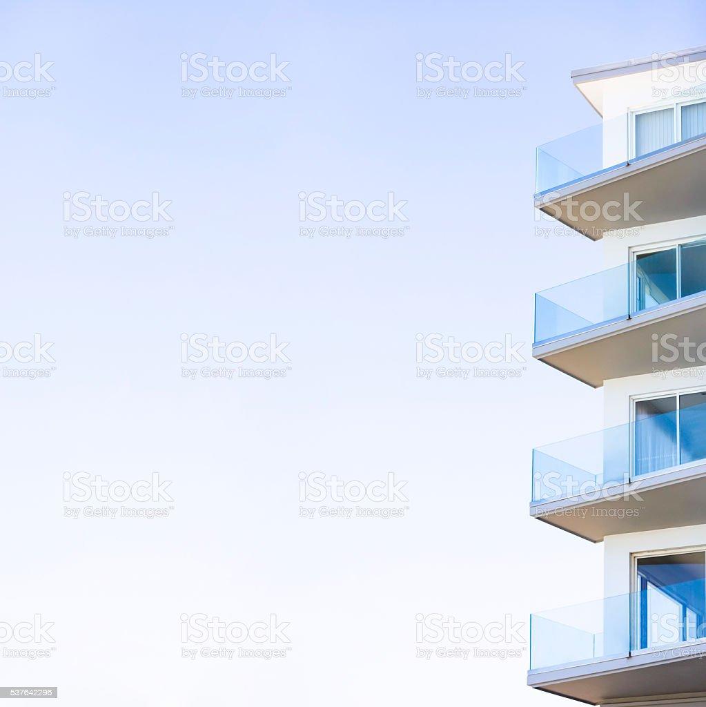 Closeup modern apartment building against blue sky, copy space stock photo