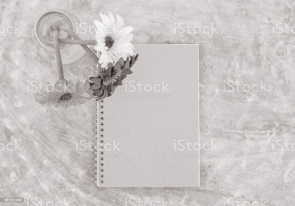 Closeup note book with blurred artificial colorful flower stock photo