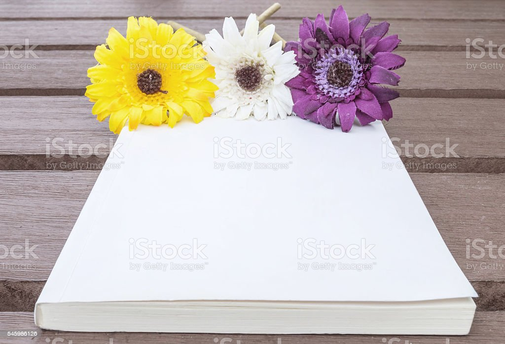 Closeup note book with colorful faked flower on wood table stock photo