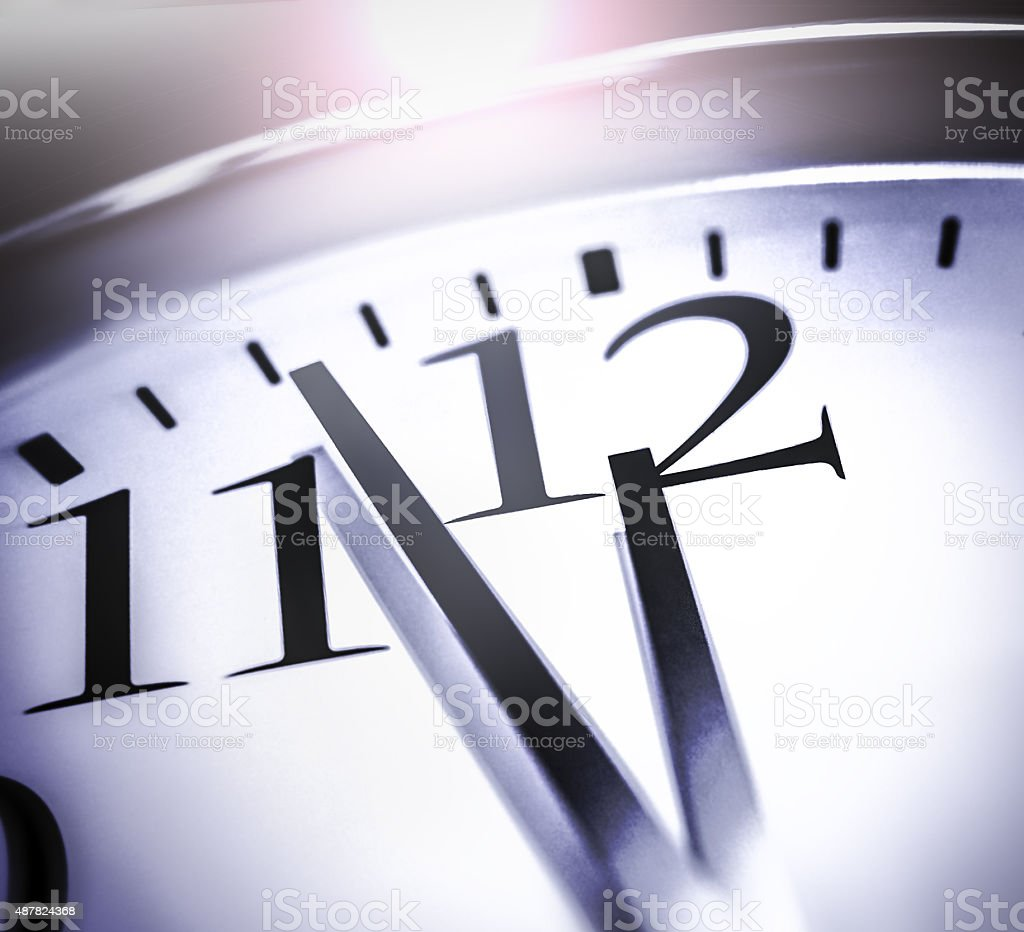 Closeup of 12 on a clock signifying a deadline. stock photo