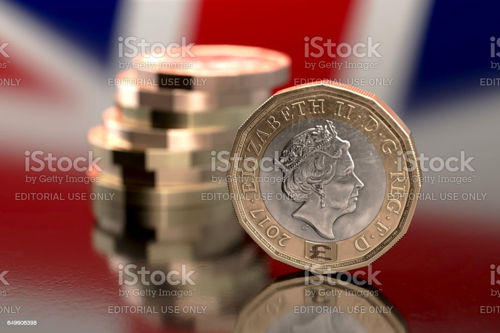 Bristol, UK - March 5, 2017: Close-up of a 2017, bi-metallic one pound coin against a small stack of coins with a reflection of the British flag in the background. stock photo