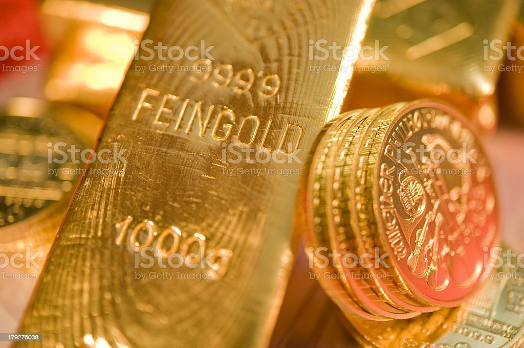 Close-up of a bar of gold next to some gold coins royalty-free stock photo