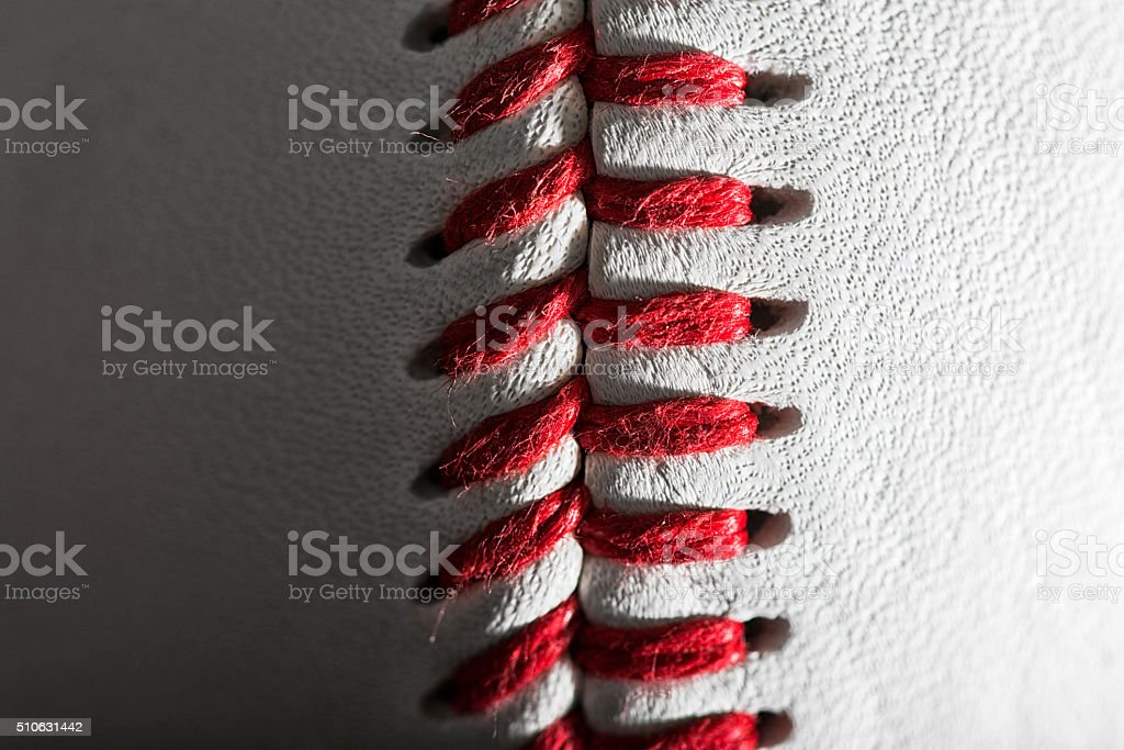 Close-up of a baseball's red stitches against a white background stock photo