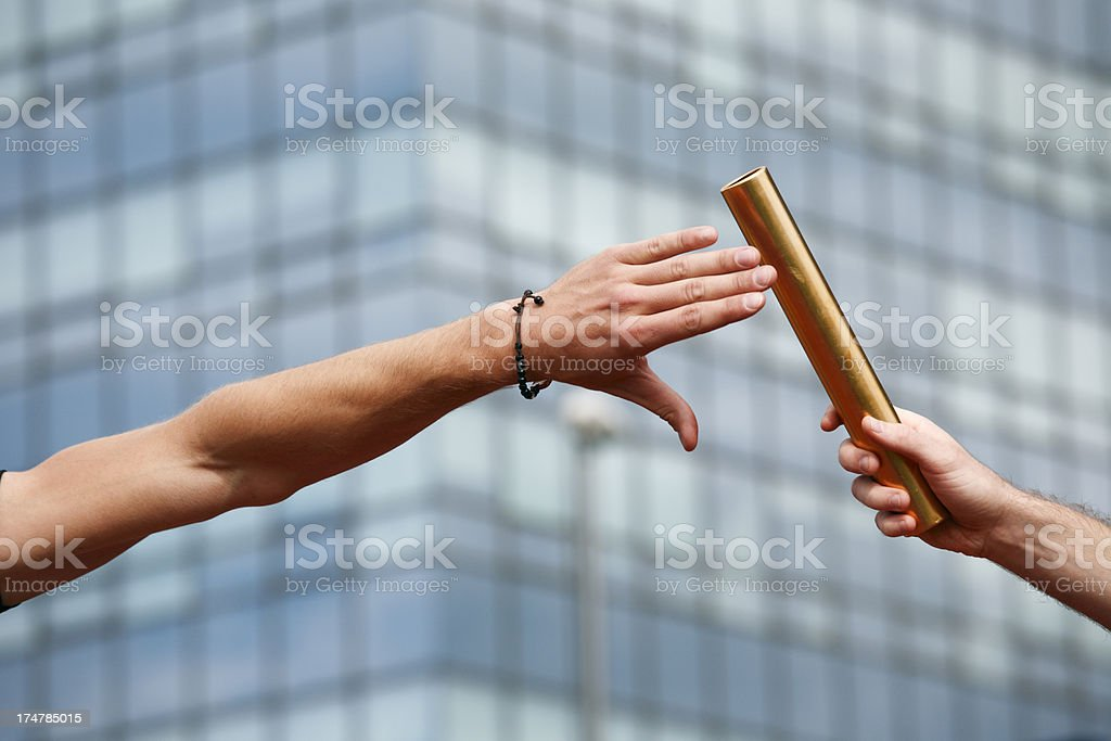 Close-up of a baton exchanging hands royalty-free stock photo