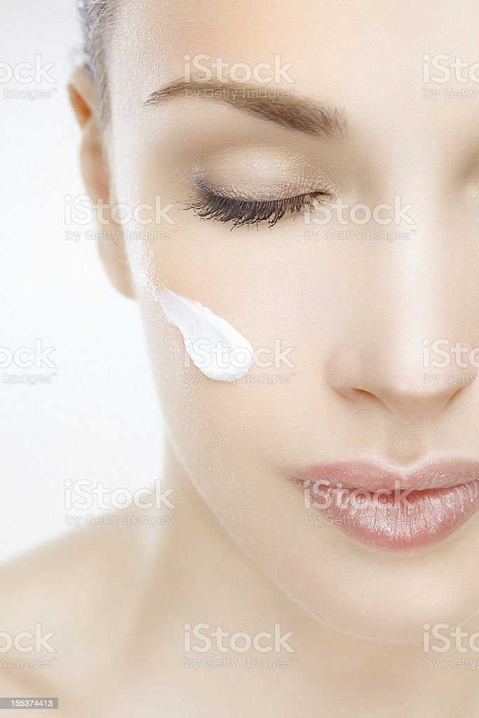 Close-up of a beautiful woman with cream on her face stock photo