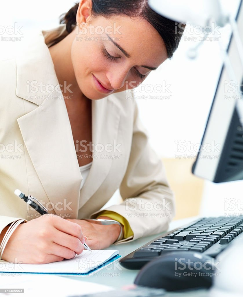 Closeup of a beautiful young business woman at desk writing on a book stock photo