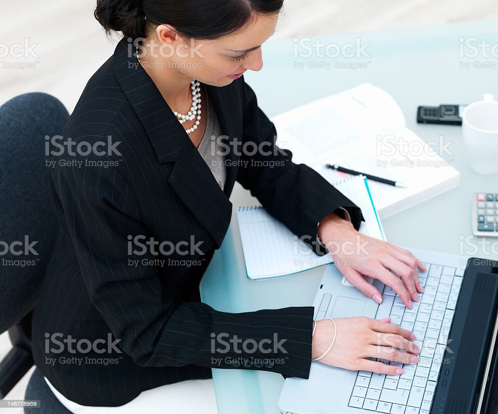 Close-up of a beautiful young businesswoman using laptop in office royalty-free stock photo