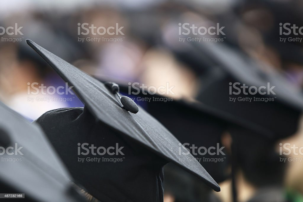 Close-up of a black graduation cap in a crowd of graduates stock photo
