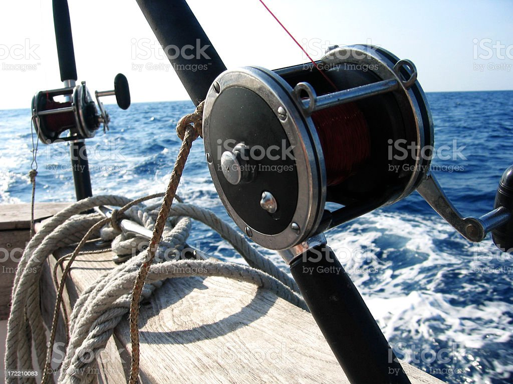 Closeup of a black, professional fishing reel on boat stock photo