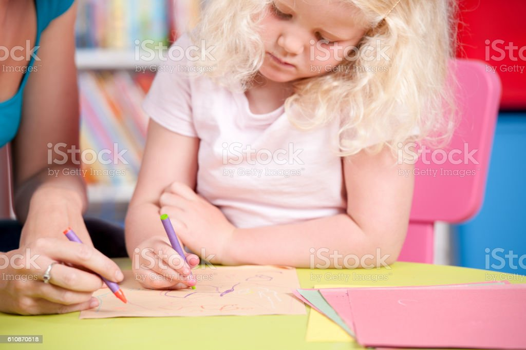 Close-up Of A Blonde Little Girl Drawing stock photo