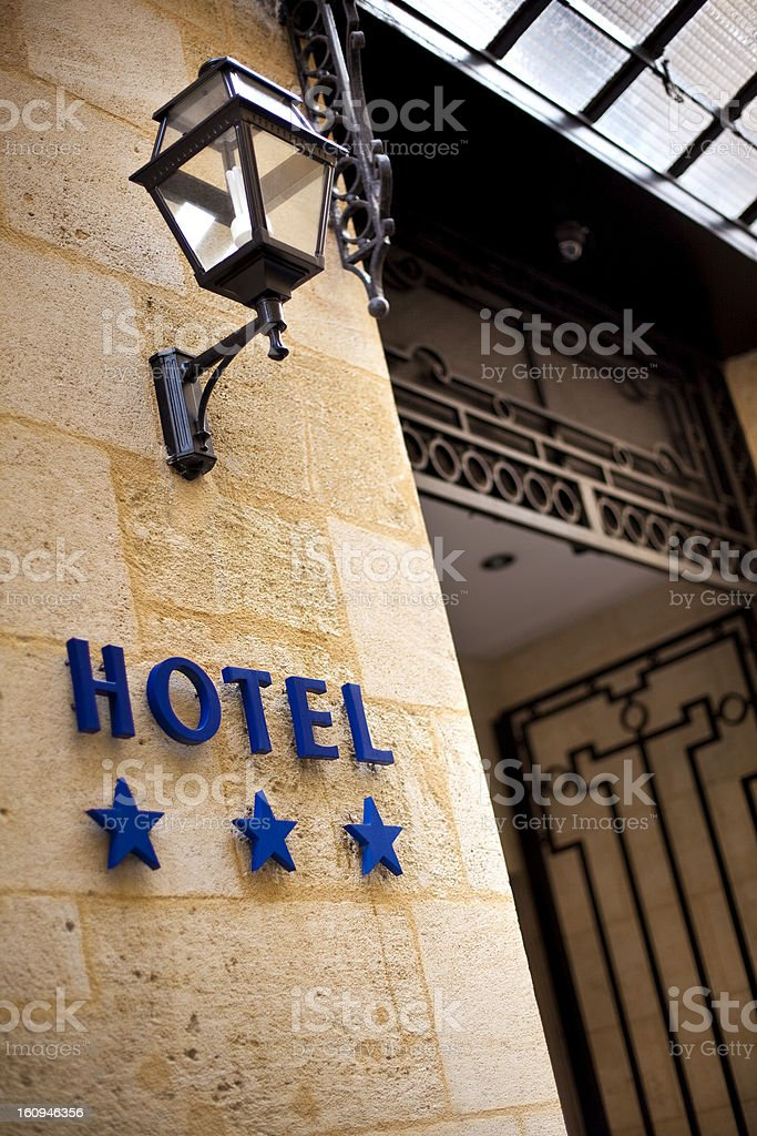 Close-up of a blue hotel sign with three stars on stone wall royalty-free stock photo