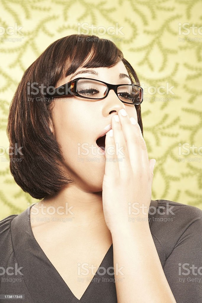 Close-up of a bored woman in eyeglasses yawning royalty-free stock photo