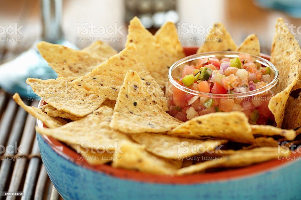 A close-up of a bowl of chips and salsa stock photo
