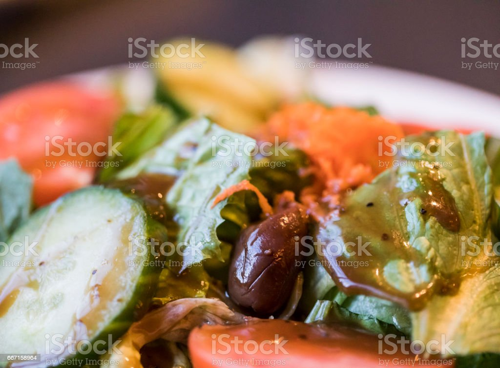 Close-up of a bowl of homemade Mediterranean salad made with fresh vegetables such as Romaine lettuce, tomatoes, cucumbers, carrots and Kalamata olives. stock photo