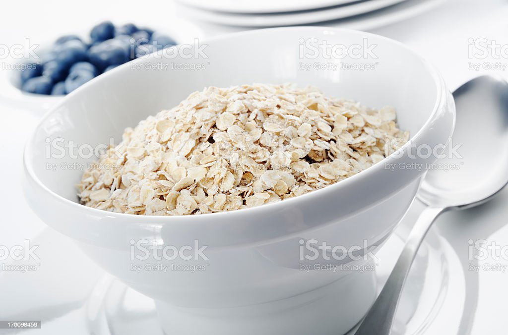 Close-up of a bowl of oatmeal and blueberries in the back royalty-free stock photo
