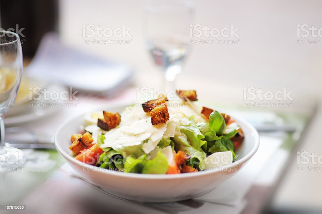 A close-up of a bowl of salad with Parmesan cheese stock photo