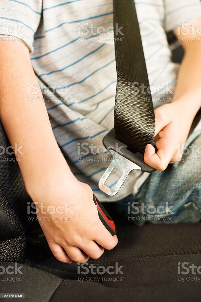 Closeup of a boy fastening his seatbelt stock photo