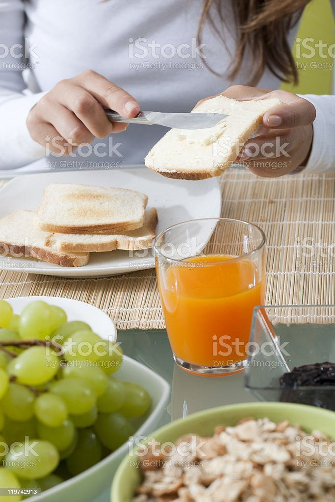 Close-up of a breakfast table with hands buttering toast royalty-free stock photo