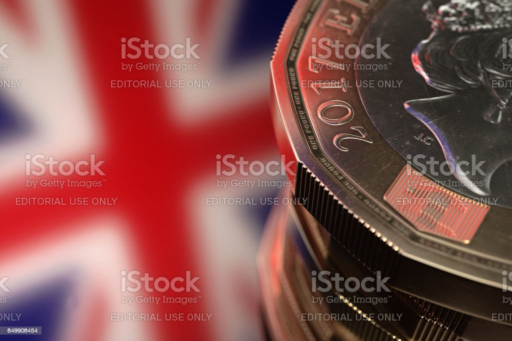 Bristol, UK - March 3, 2017: Close-up of a British 2017, bi-metallic one pound coin with the British flag in the background. stock photo