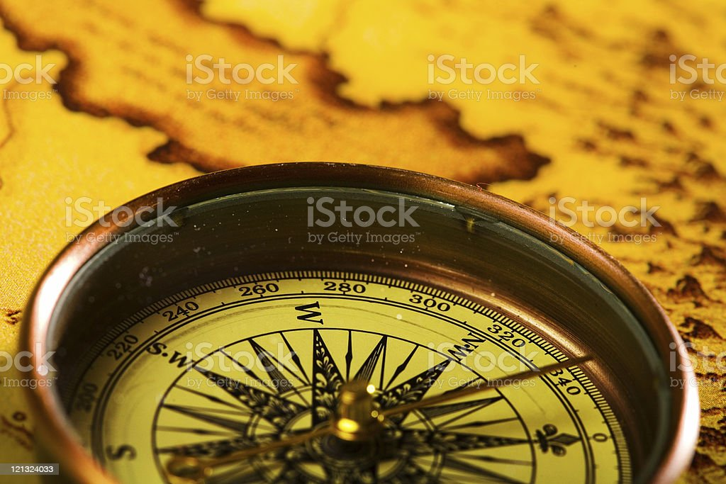 Close-up of a bronze compass laying on a map stock photo