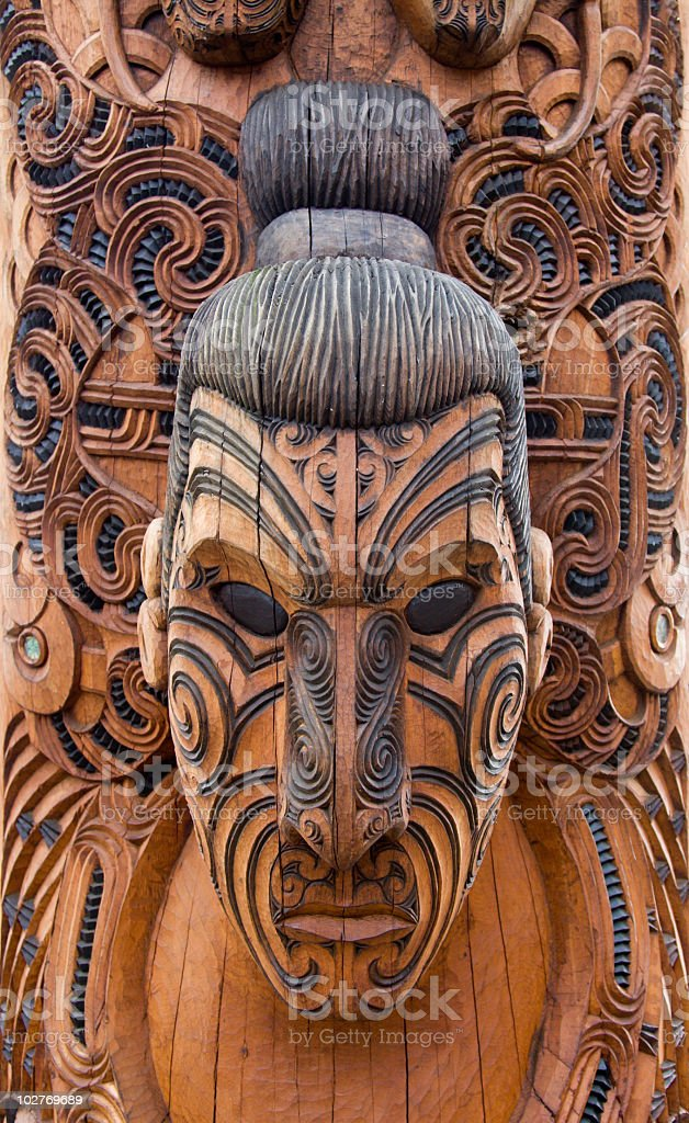 Close-up of a brown and black Maori carving of a man stock photo